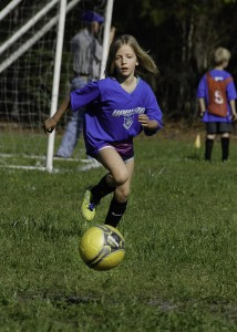 six year old pursues the soccer ball downfield at full speed